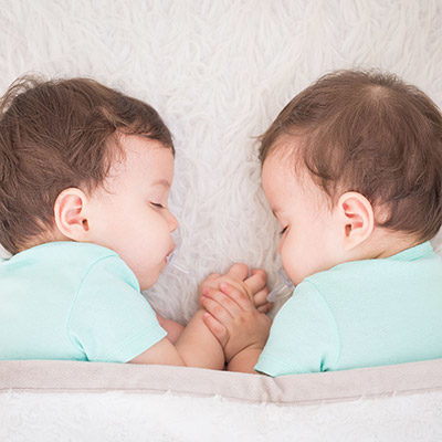 twin-babies-holding-hands