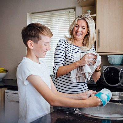 Young Man Helping Mother With Dishes